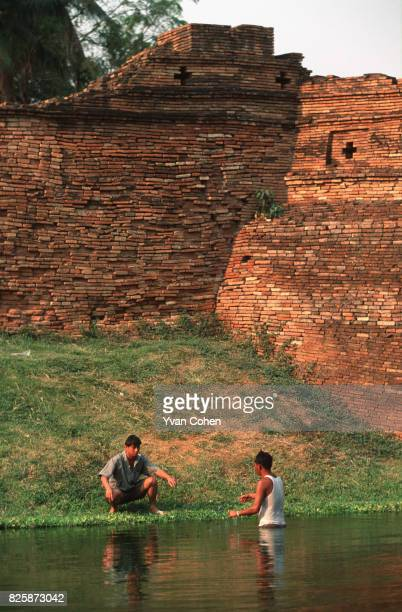Two men fish in the moat around the ancient wall that once demarcated the limits of Chiang Mai city Today Chiang Mai Thailand's northern capital has...