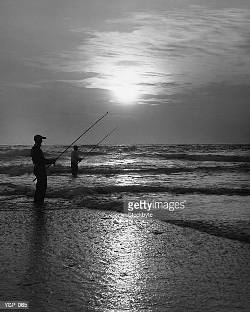 Due uomo pesca dalla spiaggia al tramonto