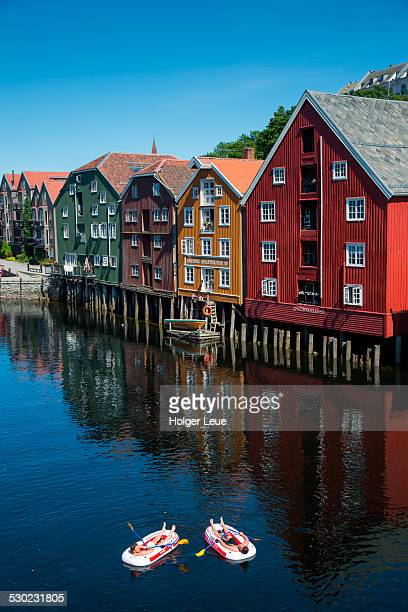 Two men float on rafts past wharves along Nidelva