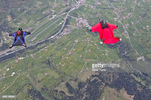 Two men flying above fields in wingsuits
