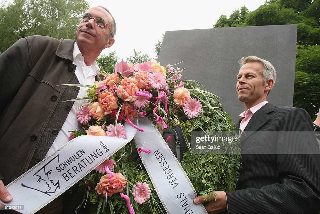 Two men from a gay councilling organization hold a wreath while lining up to peek into the window of the just-inaugurated memorial to homosexual victims of the Nazis on May 27, 2008 in Berlin, Germany. The memorial, a large stone with a window that looks onto an image of two men kissing, commemorates the tens of thousands of gays imprisoned by the Nazis, including the estimated 15,000 sent to concentration camps. The memorial stands in the Tiergarten park close the to Holocaust Memorial.