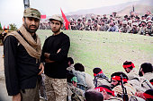 Two men from the new generation of Iran's Revolutionary Guard Corps stand in front of a huge banner showing the combatants on the battlefield during...