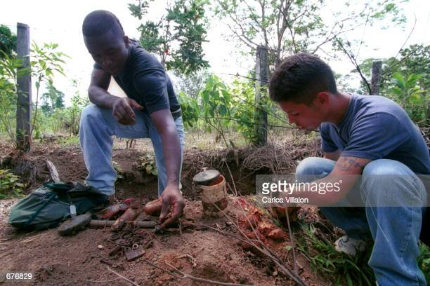 Two men from the United Colombian Self Defense Forces of Colombia deactivate a home made land mine December 14 2000 in the village of Los Angeles...