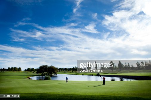 Two men golfing on a green.