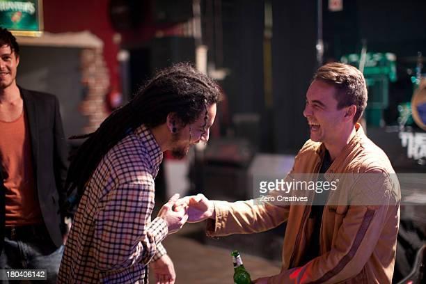 Two men greeting in bar