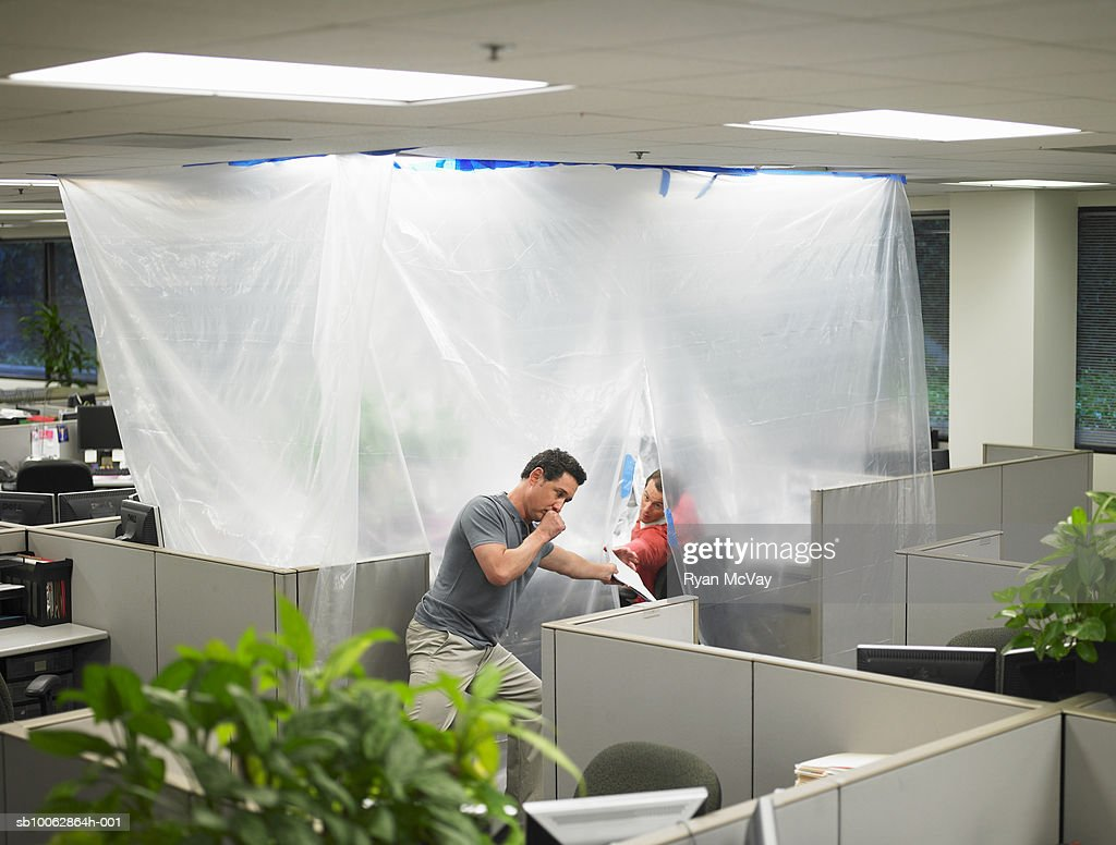 Two men handling papers in cubicle isolated by thick plastic sheeting : Stock Photo