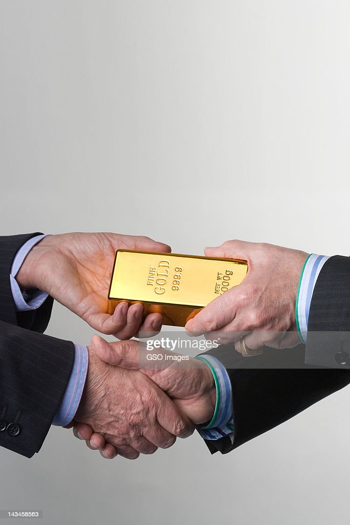 Two men handshake on a gold exchange : Stock Photo
