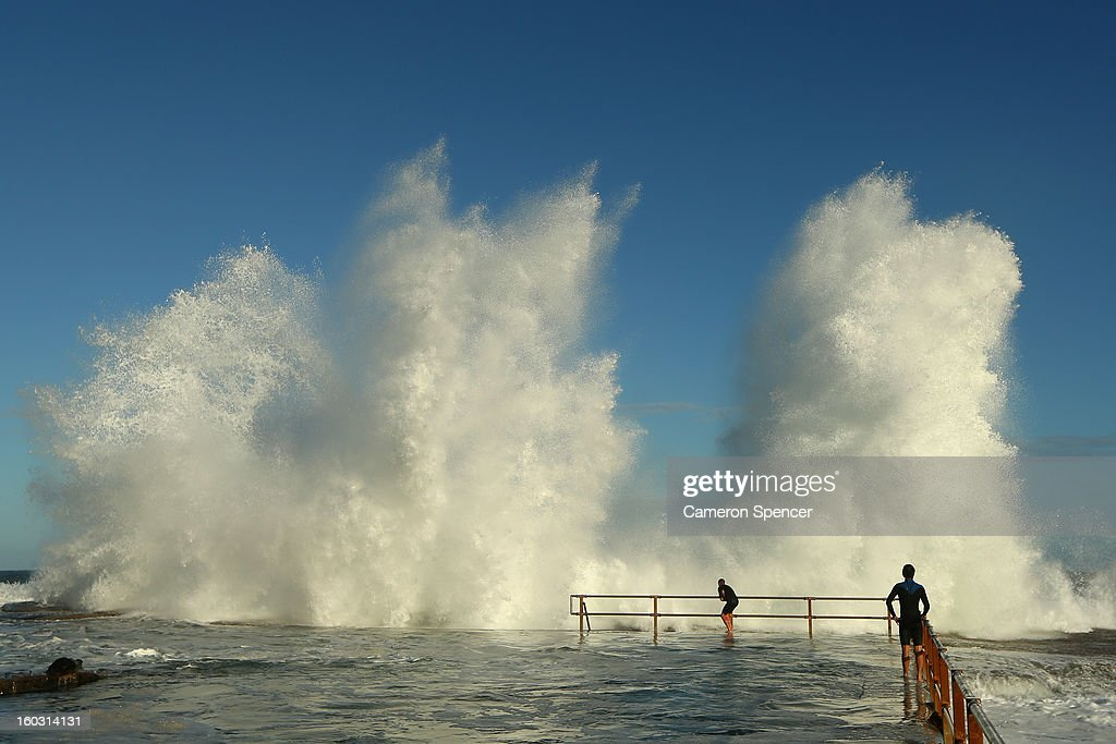Two men hang onto the railing of North Curl Curl ocean pool after winds and rain battered Sydney last night producing large swell on January 29, 2013 in Sydney, Australia. Parts of Sydney are experienced record rainfall after ex-cyclone Oswald swept through the city last night.