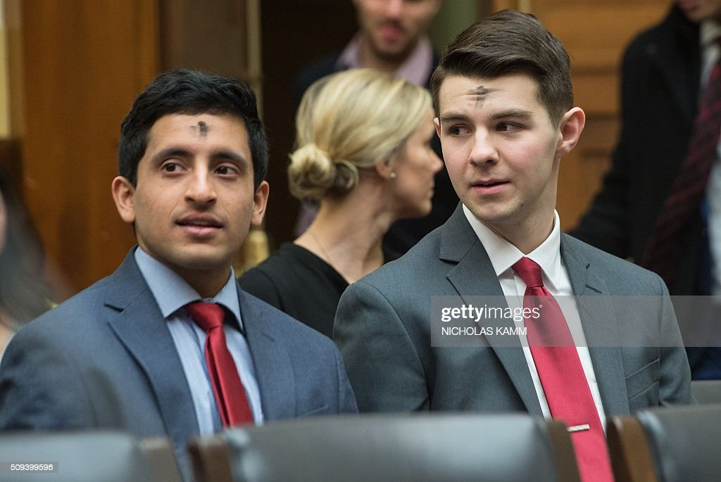 Two men have ash on their forehead as Catholics mark Ash Wednesday as they attend a hearing on Capitol Hill in Washington, DC, on February 10, 2016. / AFP / NICHOLAS KAMM