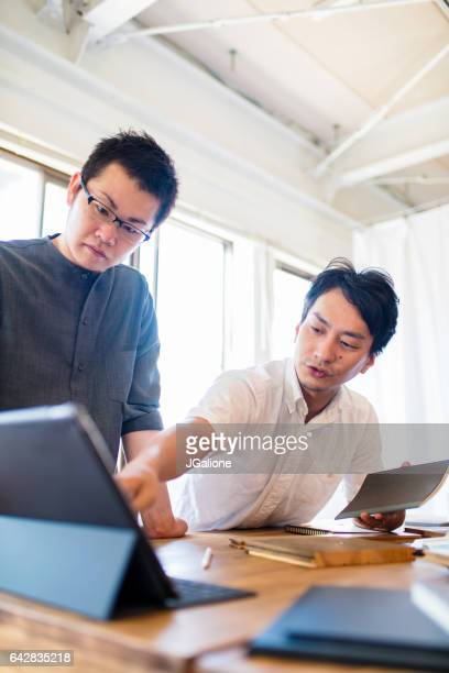 Two men having a meeting and looking at digital tablet