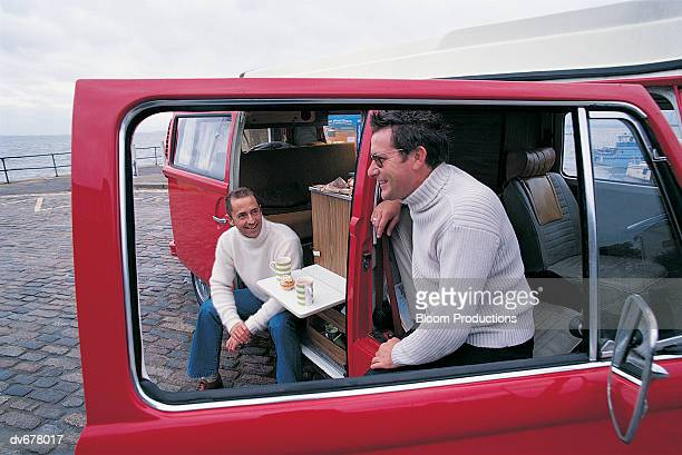 Two Men Having a Tea Break Sitting in a Van