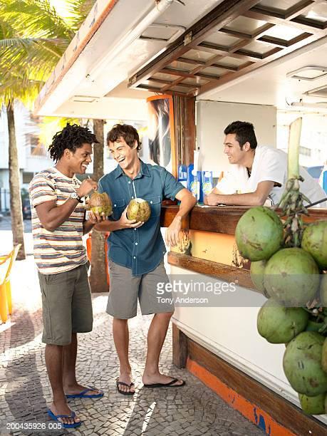 Two men having drinks, smiling