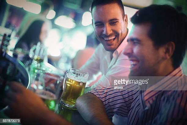 Dois homens a divertir-se numa barra.