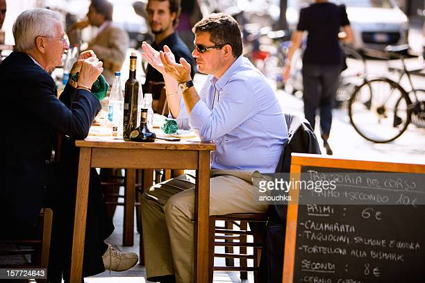 Two men having lunch in outdoor cafe, Milan, Italy