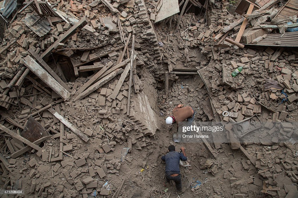 Two men help clear debris after buildings collapsed on April 26 2015 in Bhaktapur Nepal A major 78 earthquake hit Kathmandu midday on Saturday and...