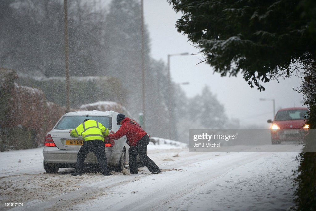 Two men help push a vehicle stuck on hill during snow on February 13, 2013 in Blanefield, Scotland. Weather forecaster have issued a yellow weather warning of up to 10cm of snow on higher routes, with the possibility of travel disruption.