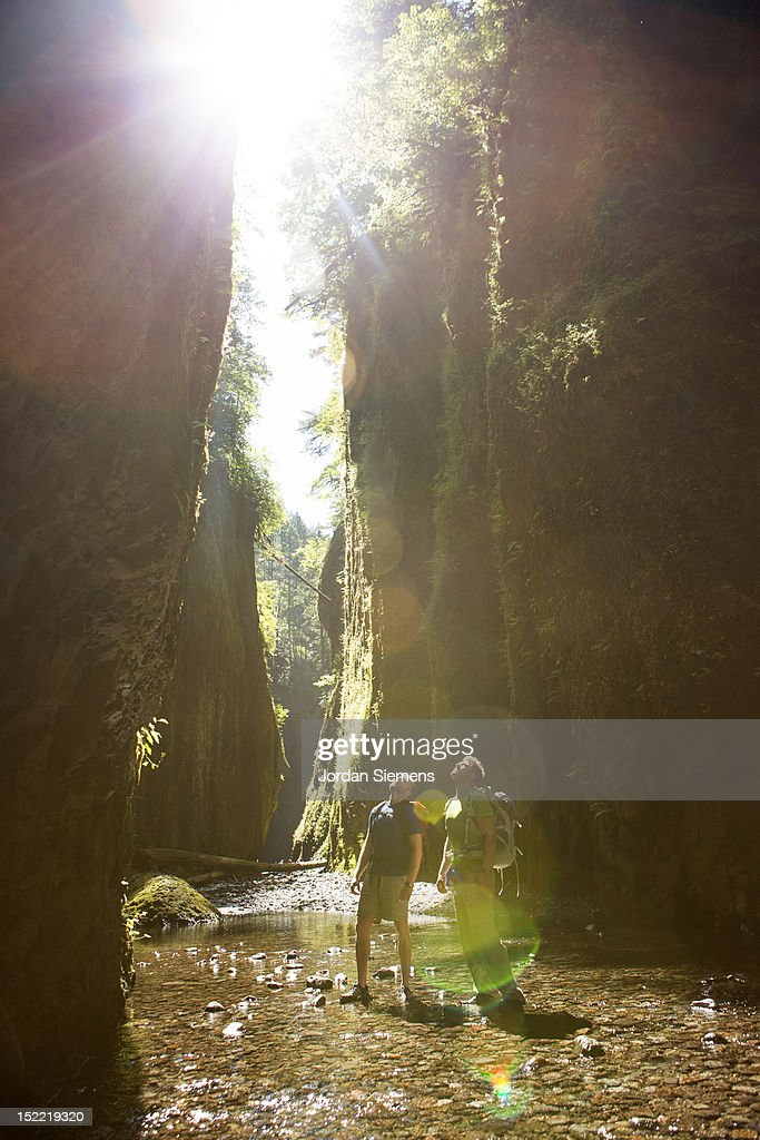 Two men hiking a canyon filled with water. : Stock Photo