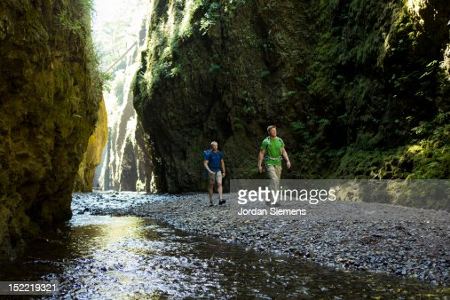 Two men hiking a narrow canyon. : Bildbanksbilder