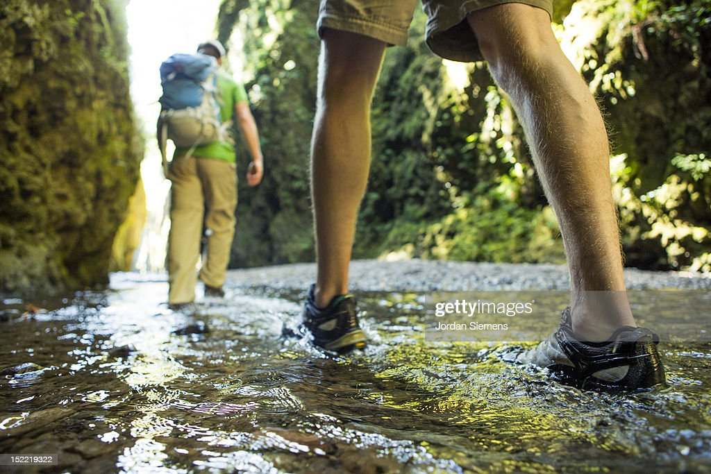 Two men hiking a narrow canyon. : Stock Photo