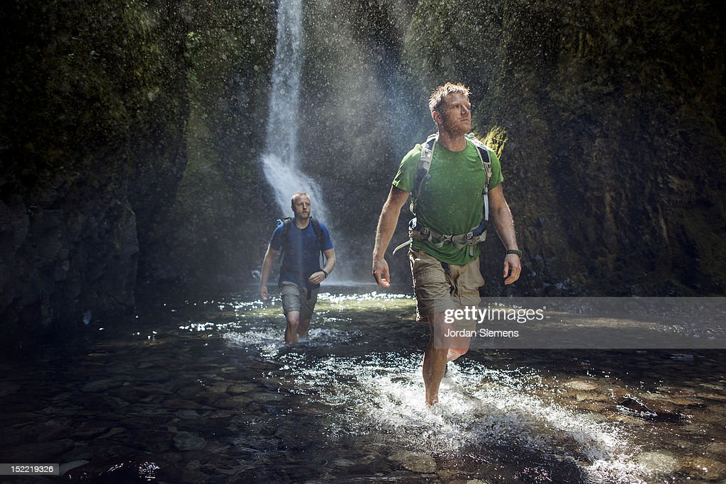 Two men hiking a narrow canyon.