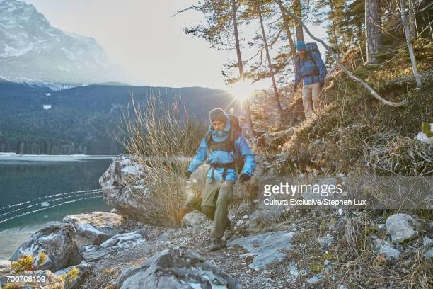 Two men hiking by Lake Eibsee in winter, Zugspitze, Bavaria, Germany
