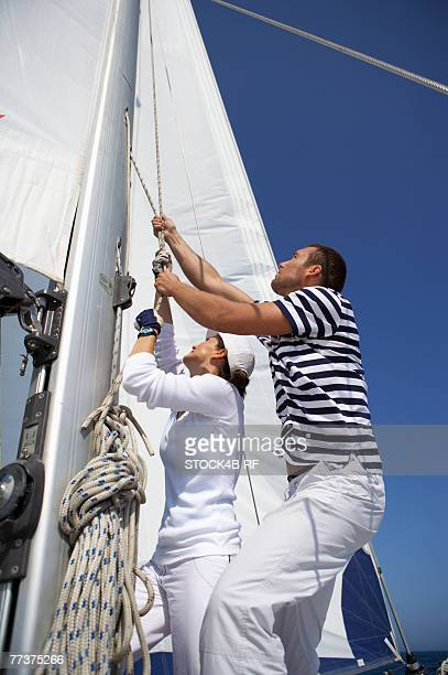 Two men hoisting a sail, low angle view