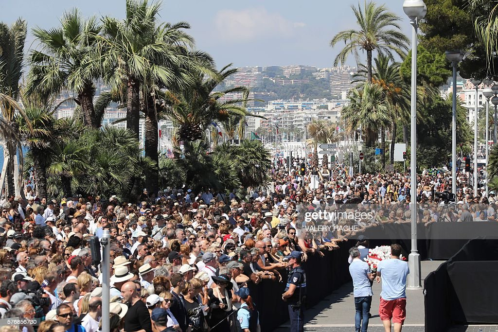 TOPSHOT - Two men hold a flower wreath as people gather to observe a minute silence at the Jardin Albert 1er on the Promenade des Anglais in Nice on July 18, 2016, in tribute to victims of the deadly Nice attack on Bastille day. France fell silent on Monday for the victims of the Nice truck attack, but the mourning was overshadowed by politicians tearing into each other over the massacre. A sea of people thronged the Nice promenade for the emotional minute's silence just days after a Tunisian attacker drove a truck into a crowd at the same place on Bastille Day, killing 84 people and injuring around 300. / AFP / Valery HACHE