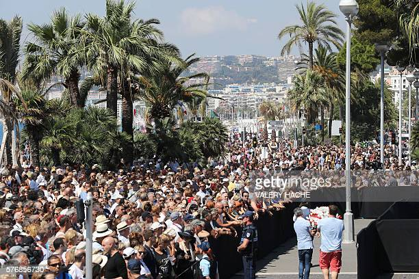 TOPSHOT Two men hold a flower wreath as people gather to observe a minute silence at the Jardin Albert 1er on the Promenade des Anglais in Nice on...