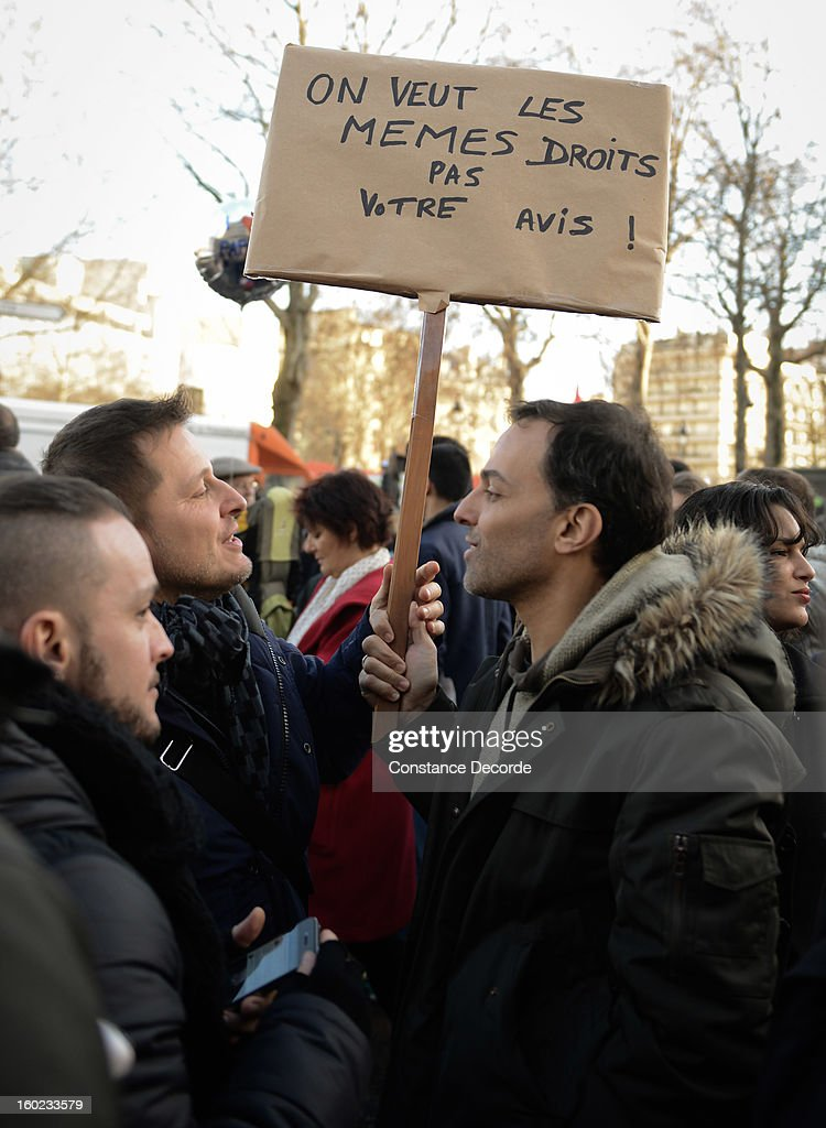 Two men hold a sign reading 'we're asking for same rights as yours, not for your opinion' during the marriage for all demonstration on January 28, 2013 in Paris, France. The marriage equality bill, which will be debated at the French National Parliament, would not only legalize same-sex marriage and also allow gay couples to adopt, a controversial issue in the bill. French President Francois Hollande supports the legislation but faces criticism from anti-gay and religious groups, while gay rights groups have concerns of inadequacies within the bill.