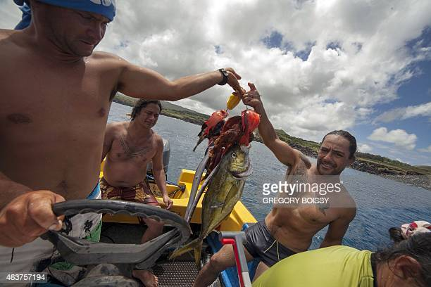 Two men hold fishes after an underwater fishing contest in Hanga Roa on Chile's Easter Island in the Pacific Ocean on February 10 2015 as part of the...