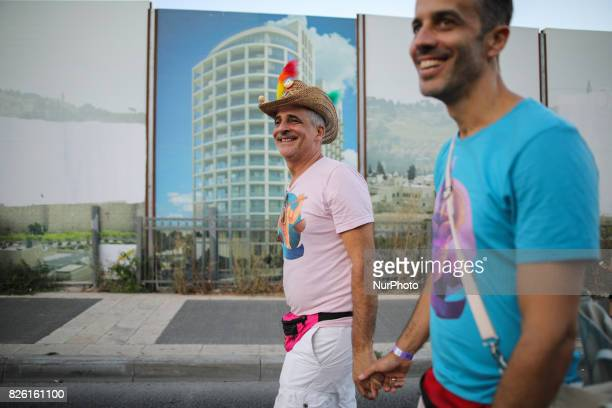 Two men hold hands as they take part in the annual Gay Pride parade in Jerusalem Israel August 03 2017 22000 March in Jerusalem Pride Parade...
