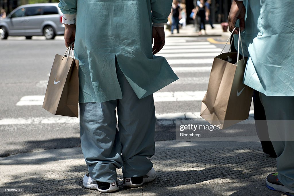 Two men hold Nike Inc. bags as they wait to cross the street in a retail area known as the 'Magnificent Mile' in Chicago, Illinois, U.S., on Tuesday, June 11, 2013. Sales at U.S. retailers probably rose in May as an improving job market gave consumers the confidence to shop for automobiles, home furnishings and clothing, economists said before reports this week. Photographer: Daniel Acker/Bloomberg via Getty Images