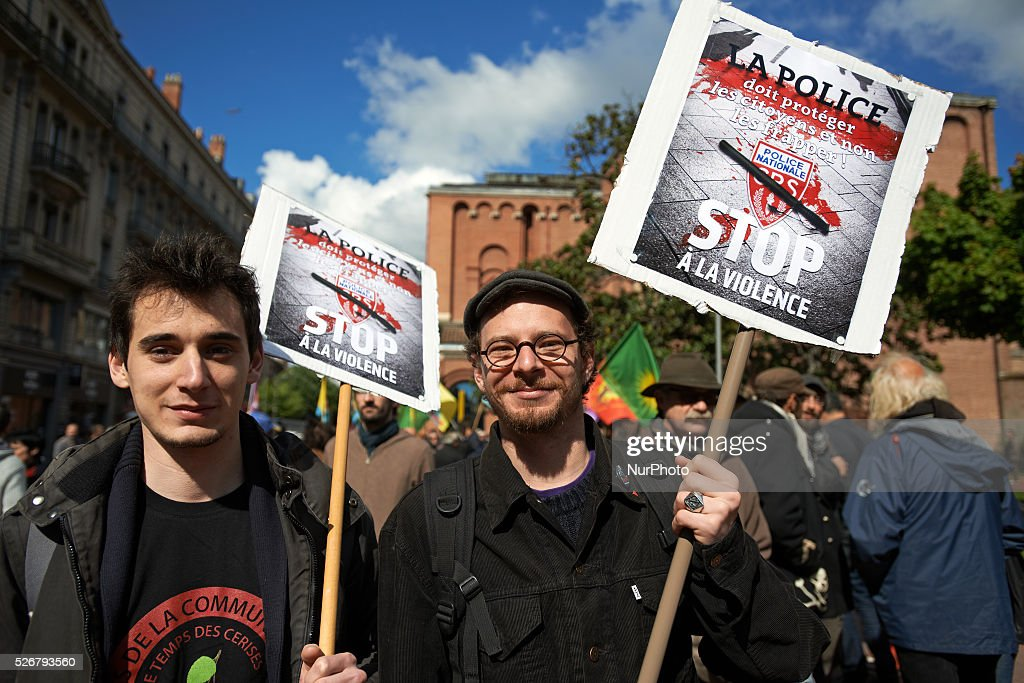 Two men hold placards of the CGT syndicate reading 'The police must protect citizens, not hur them. Stop to the violence' during the Labor Day march on May 1st. Police syndicates have condemned the placard. Toulouse. France. May 1st 2016.