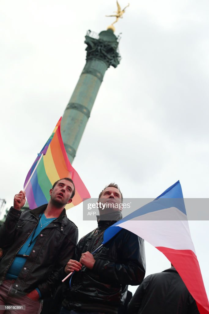 Two men holding a rainbow flag and a French national flag attend the event 'Concert pour tous!' (Concert for all!) on May 21, 2013 at the Bastille square in Paris. The 'Concert for all!' in reference of the French anti-gay marriage movement 'Manif pour tous !' (Demonstration for all!), is held to celebrate the legalisation of same-sex marriage. After months of acrimonious debate and hundreds of protests that have occasionally spilled over into violence, France's National Assembly approved on April 23, 2013 a bill making the country the 14th to legalise same-sex marriage. A placard reading 'married within the year' is seen on the ground.