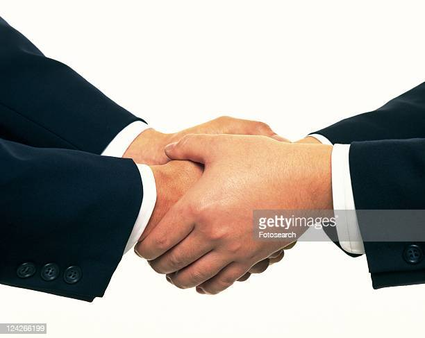 Two men holding and shaking hands, side view, close up