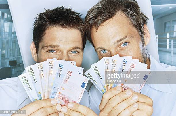 Two men holding Euro banknotes in front off faces, portrait, close-up