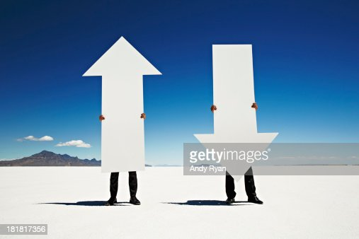 Two men holding giant arrows in desert.