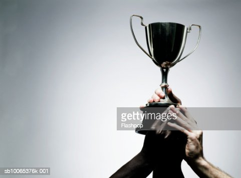 Two men holding trophy, close-up