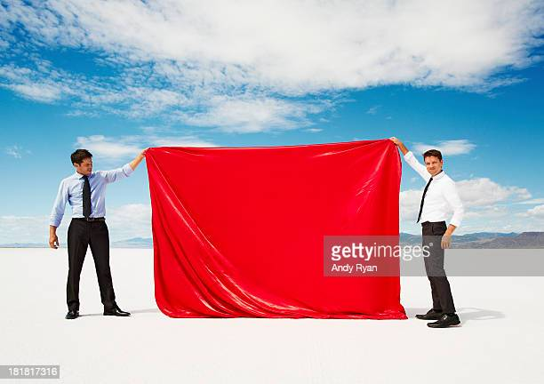 Two men holding up sheet of red fabric in desert.