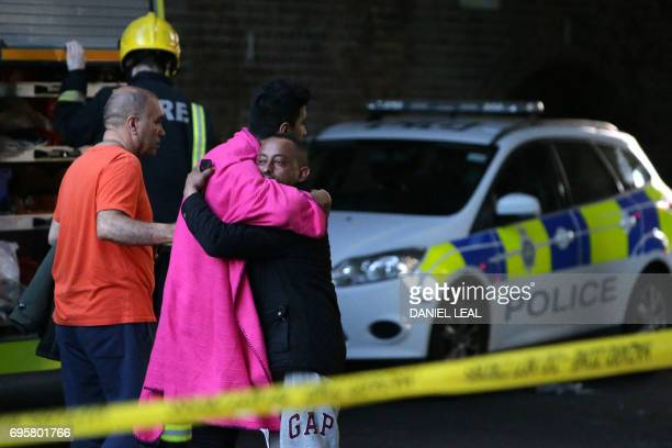 TOPSHOT Two men hug within the security cordon as Grenfell Tower is engulfed by fire on June 14 2017 in west London The massive fire ripped through...