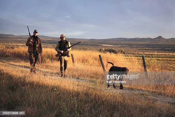 Two men hunting with Chocolate labrador