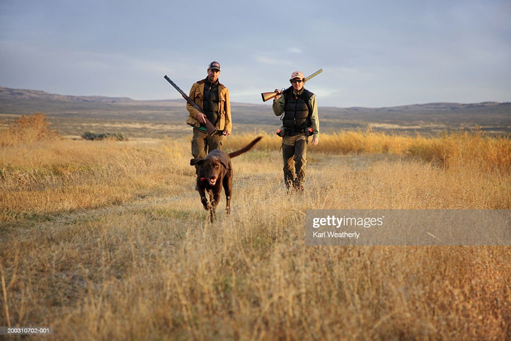 Two men hunting with Chocolate labrador, portrait