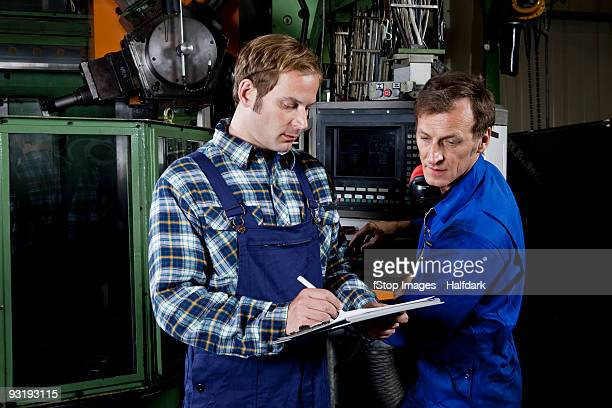 Two men in a metal parts factory reviewing a clipboard
