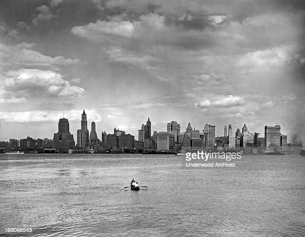 Two men in a rowboat with an American flag for a bowsprit head off from New Jersey across the Hudson River towards Lower Manhattan New York New York...
