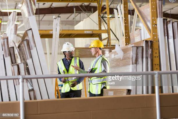 Two men in a warehouse of construction supplies talking