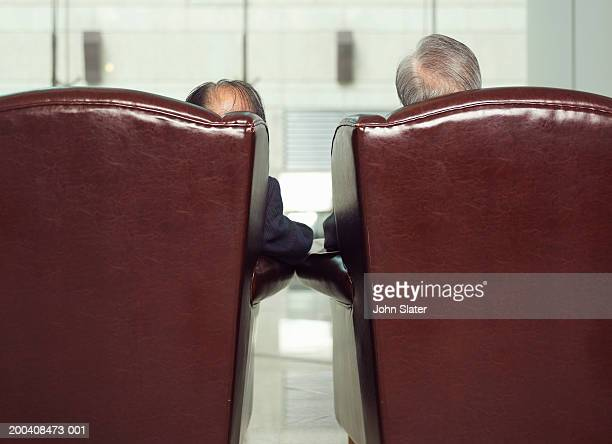 Two men in arm chairs, rear view