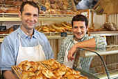Two men in bakery, one holding tray with croissants, smiling, portrait