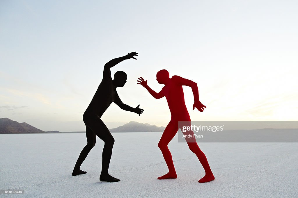 Two men in bodysuits grappling in desert.