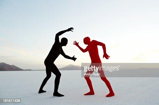 Two men in bodysuits grappling in desert.