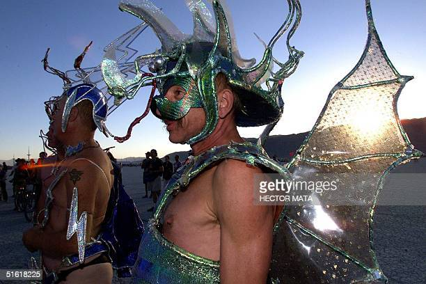 Two men in costume walk on the desert at Black Rock City's Burning Man festival in Nevada 04 September 1999 Founded in 1986 by a group of fine...